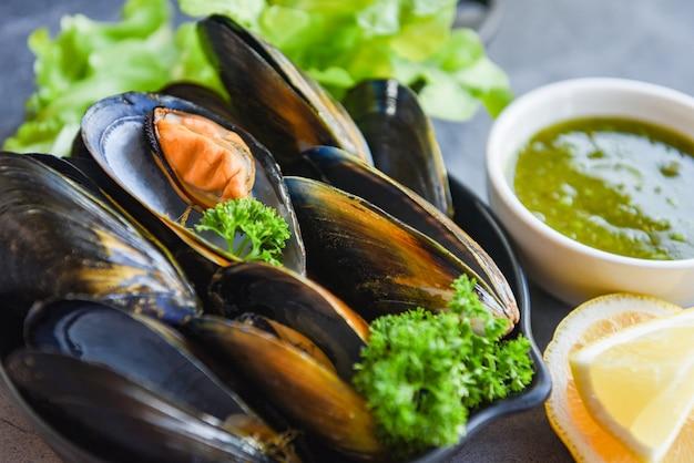 Gekochte miesmuscheln mit kräutern zitrone und dunklem plattenhintergrund - frische meeresfrüchteschalentiere auf schüssel und würziger soße im restaurantmuschel-oberteillebensmittel