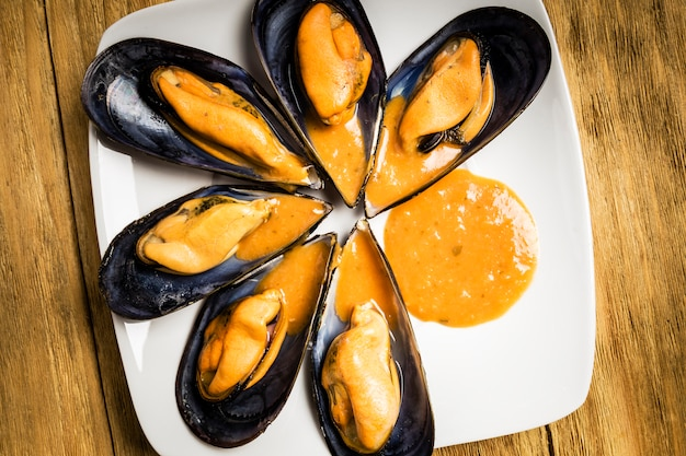 Gekochte miesmuscheln mit petersilie und orangensauce und eine halbe zitrone auf einer weißen platte