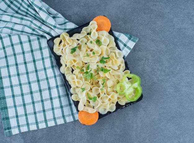 Gekochte nudeln mit gemüse auf schwarzem teller.