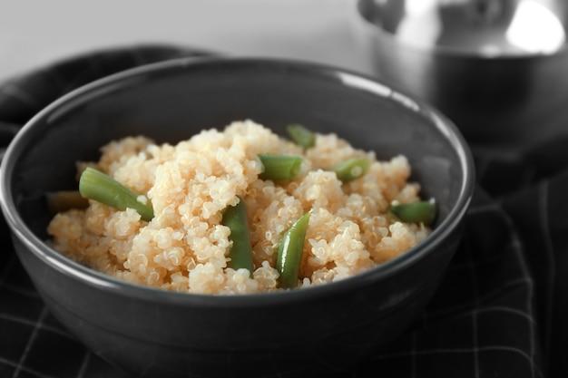 Gekochte quinoa mit französischen bohnen in schwarzer schüssel