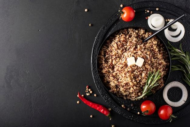 Gekochte quinoa mit gewürzen, öl und gemüse in einer schwarzen schüssel, draufsicht