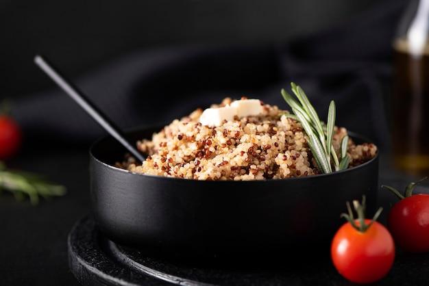Gekochte quinoa mit gewürzen und gemüse in einer schwarzen schüssel