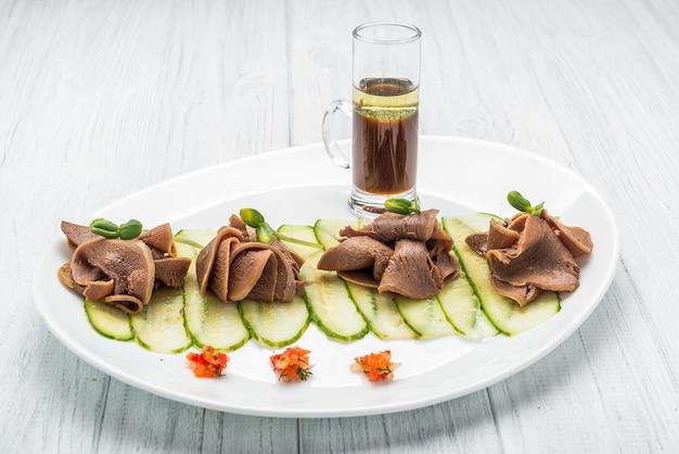 Gekochte rinderzunge auf dunklem holztisch mit pesto und salat