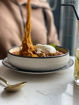 Gekochte spaghetti auf einer gabel, weichzeichner und unscharfer hintergrund. vertikal