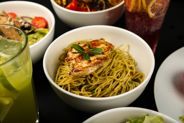 Gekochte spaghetti mit gebratenem huhn in tiefem teller