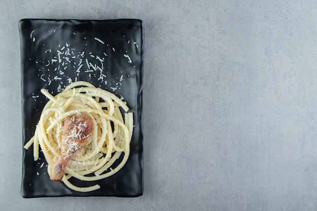 Gekochte spaghetti-nudeln auf schwarzem teller.