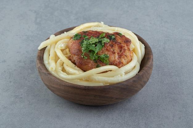 Gekochte spaghetti-nudeln und gebratenes huhn in holzschale.