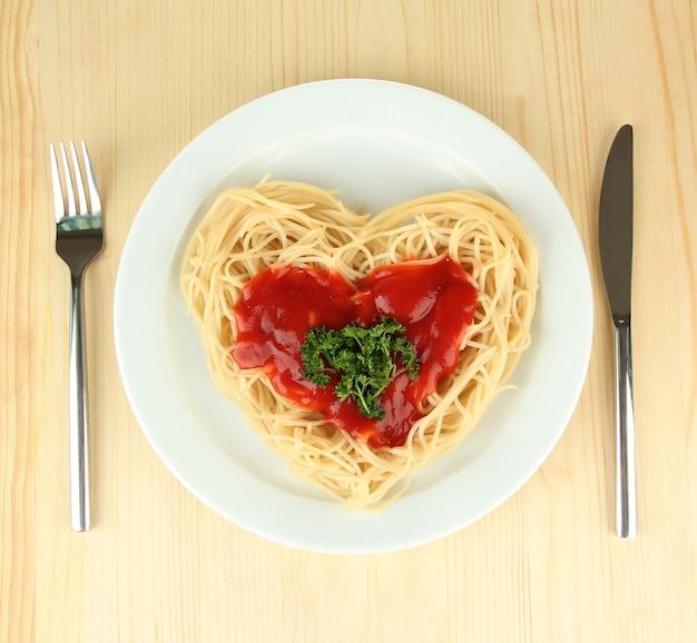 Gekochte spaghetti sorgfältig in herzform angeordnet und mit tomatensauce auf holzfläche belegt
