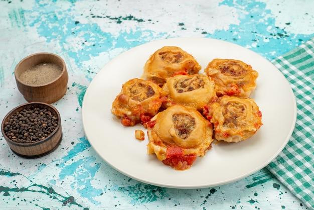 Gekochte teigmahlzeit mit hackfleisch in teller mit paprika auf hellblauem schreibtisch, teigmahlzeit essen fleischkalorie