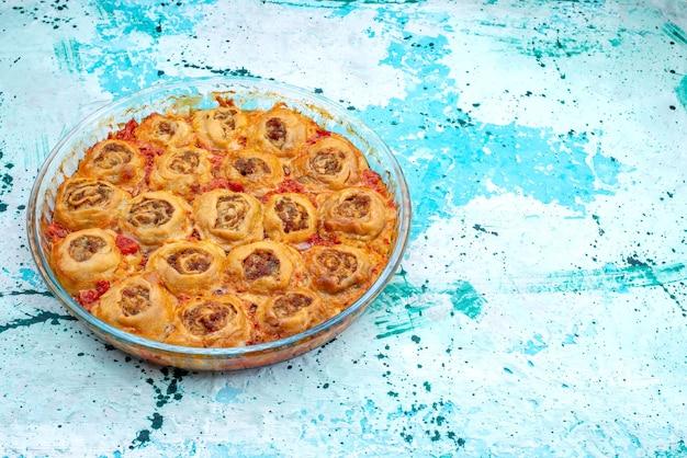 Gekochte teigmahlzeit mit hackfleisch und tomatensauce in der glaspfanne auf hellblauem backteig-fleischteig