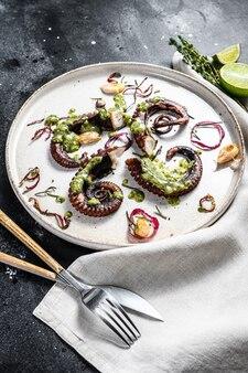 Gekochte tintenfischtentakeln mit pesto, thymian und zwiebeln