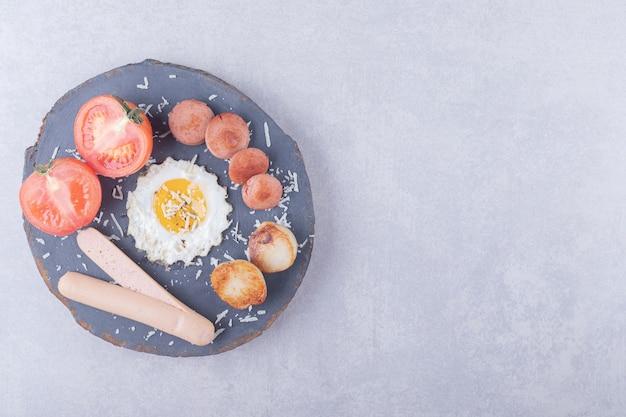 Gekochte und gebratene würstchen mit ei auf holzstück.