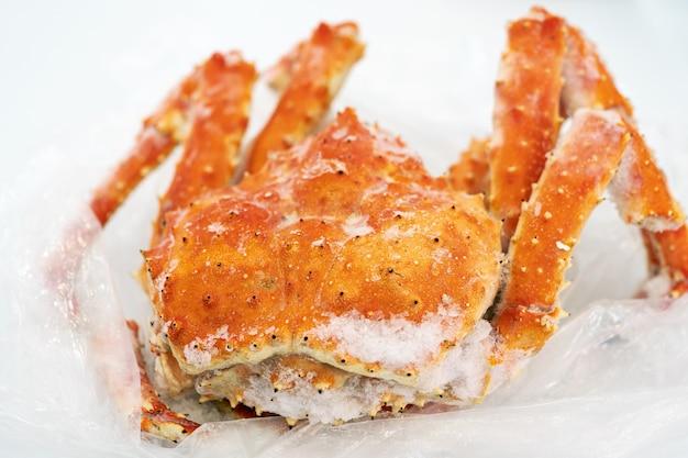 Gekochte und gefrorene wilde rote königskrabbe liegt auf plastikverpackungen im kühlschrank. alaska-königskrabbe oder kamtschatka-krabbe - beliebte und teure meeresdelikatesse. nahaufnahme von leckeren meeresfrüchten.