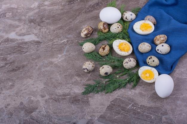 Gekochte und rohe eier auf einem blauen taschentuch