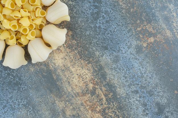 Gekochte und ungekochte nudeln in der schüssel auf dem marmorhintergrund.