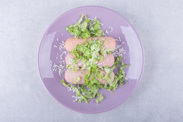 Gekochte würste dekoriert mit salat auf lila teller.
