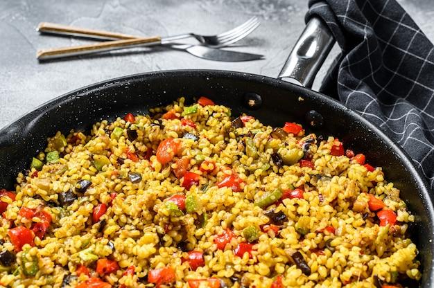 Gekochter bulgur mit gemüse und hühnerfleisch in einer pfanne. grauer hintergrund.