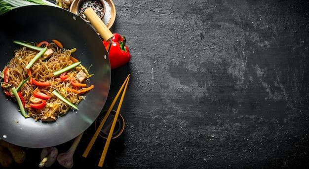 Gekochter chinesischer nudel-cellophan-wok mit sojasauce in einer schüssel und mit stäbchen. auf schwarzer rustikaler oberfläche