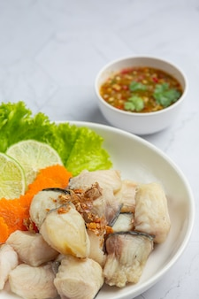 Gekochter fisch mit würziger dip-sauce und gemüse