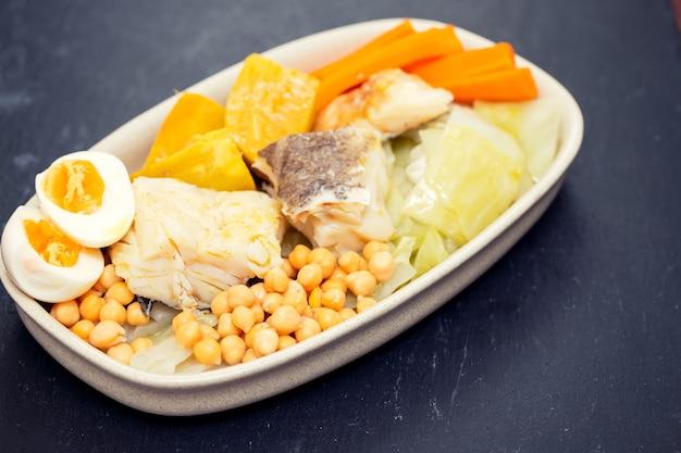 Gekochter kabeljau mit gekochtem gemüse auf teller