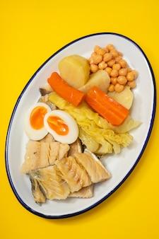 Gekochter kabeljau mit gekochtem gemüse und ei auf weißem teller