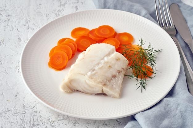 Gekochter kabeljau mit karotte und dill auf weißer platte