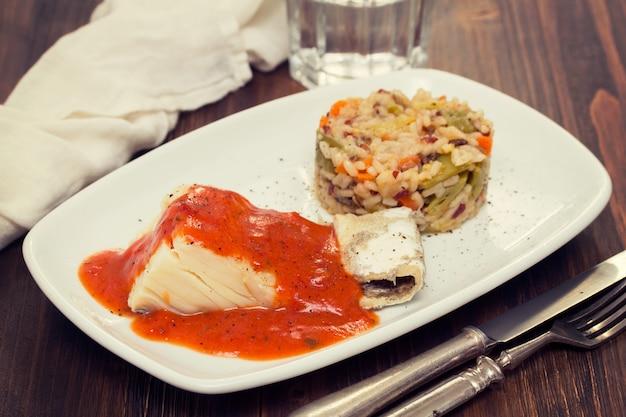 Gekochter kabeljau mit tomatensauce und reis auf teller