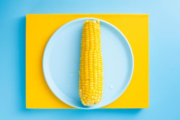 Gekochter mais auf einer blauen platte