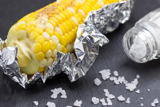 Gekochter mais in folie. salzstreuer und salz auf dem tisch. schwarzer hintergrund. nahaufnahme