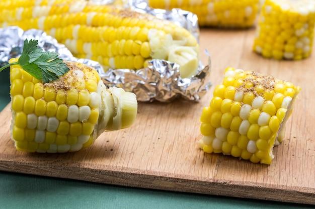 Gekochter mais und gekochter mais in folie auf holzbrett. grüner hintergrund. nahaufnahme