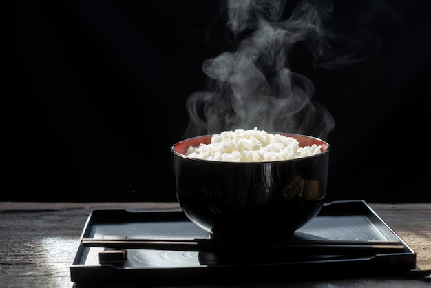 Gekochter reis mit dampf in der schwarzen schüssel auf dunklem hintergrund, heißer gekochter reis im selektiven fokus der schüssel, warme küche und gesundes