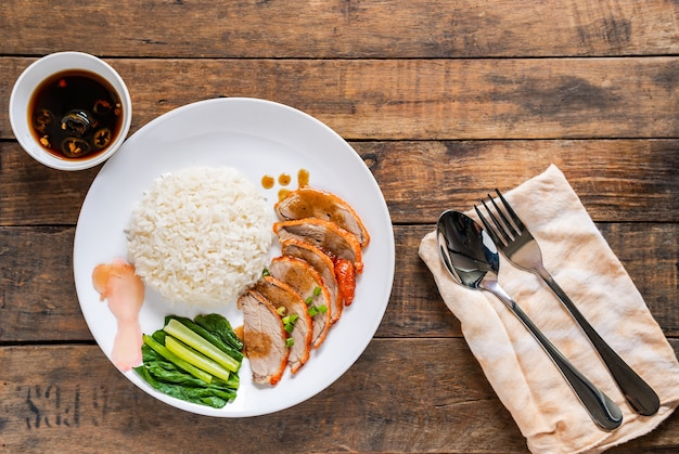 Gekochter reis mit gebratener ente auf weißem teller und traditionellem thailändischem essen des alten hölzernen schreibtisches.