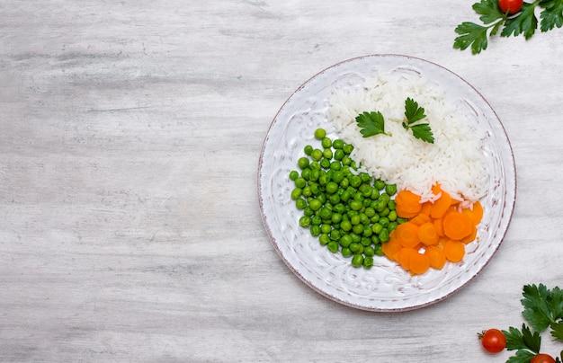 Gekochter reis mit gemüse und petersilie auf platte auf tabelle