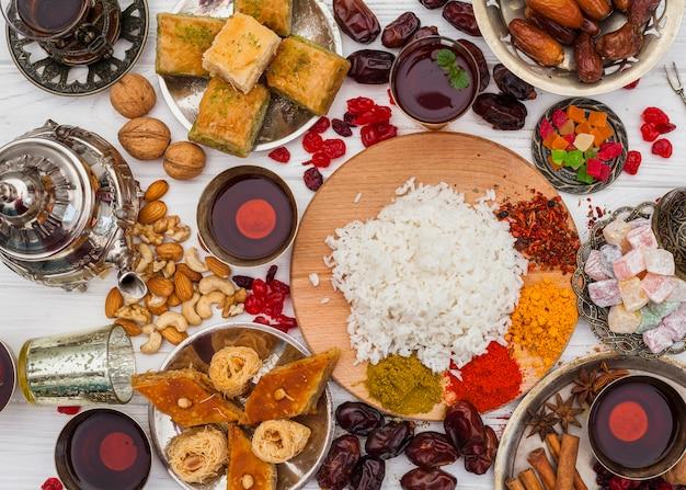 Gekochter reis mit gewürzen und süßigkeiten auf dem tisch