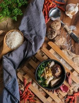 Gekochter reis mit schweinefleisch, pornoknochen und thailändischer schweinswurst in der schüssel