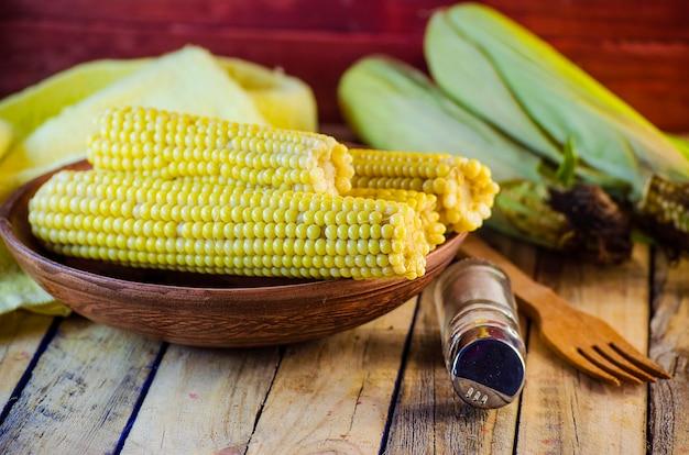 Gekochter süßer junger mais auf einem teller und salz