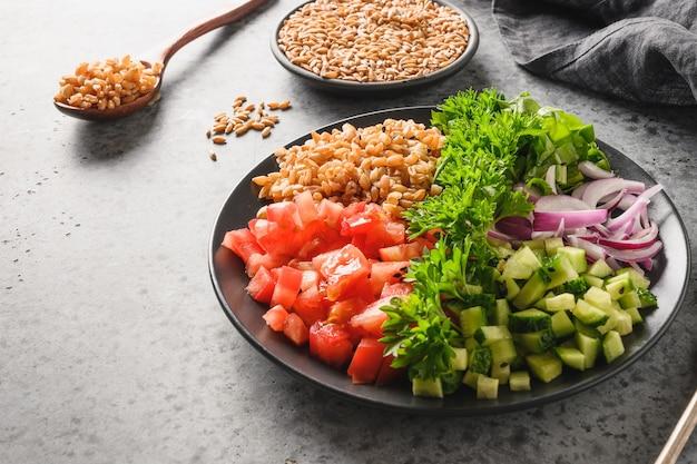 Gekochter vollkorn-müsli-dinkel-salat mit saisonalem gemüse in der schüssel auf schwarzem hintergrund.