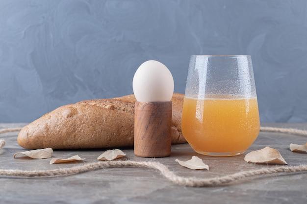 Gekochtes ei, brot und ein glas saft auf marmortisch.