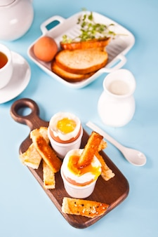 Gekochtes ei im eierbecher auf holzbrett mit knusprigem toast