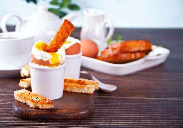 Gekochtes ei in eierbecher auf holzbrett mit knusprigem toast.