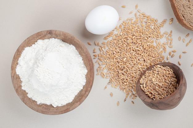Gekochtes ei mit haferkörnern und holzschale voller mehl