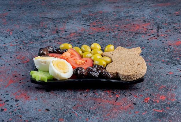 Gekochtes ei mit schwarzen und grünen marinierten oliven und tomaten.