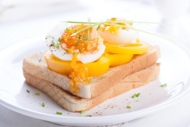 Gekochtes ei mit tomaten auf scheibe brot