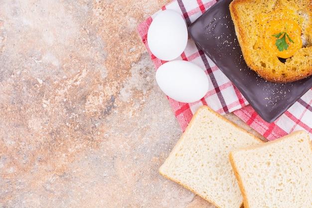 Gekochtes ei und brot auf einer platte auf einem geschirrtuch auf dem marmor.
