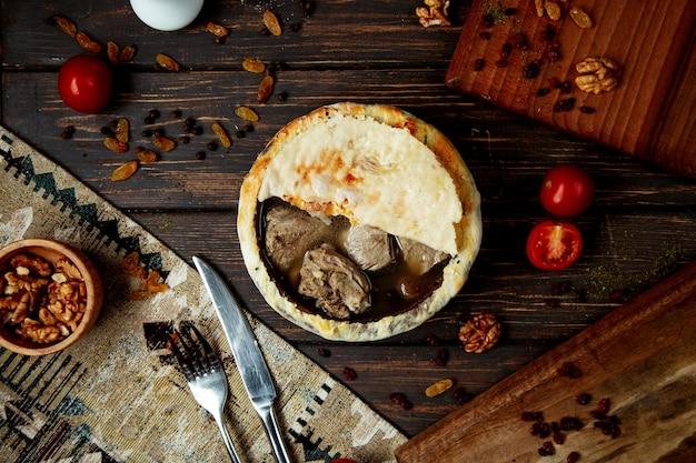 Gekochtes fleisch in mit brot bedeckten tontöpfen