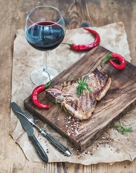 Gekochtes fleisch-t-bone-steak auf servierbrett mit gerösteten tomaten