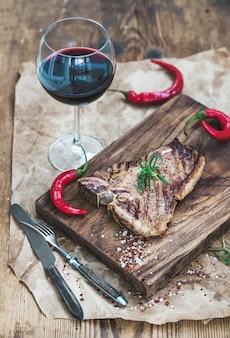 Gekochtes fleischknochensteak auf umhüllungsbrett mit gebratenen tomaten, paprikapfeffern, frischem rosmarin, gewürzen und glas rotwein über rustikaler holzoberfläche