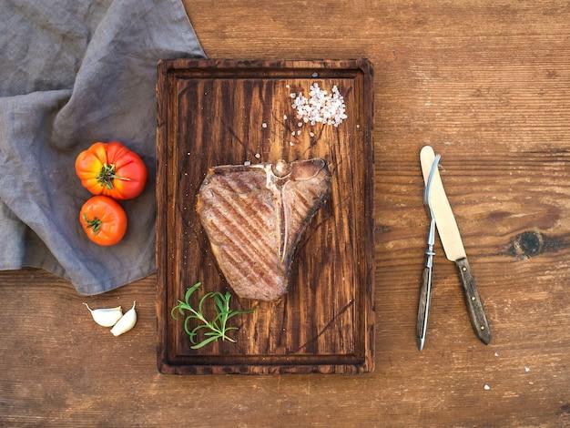 Gekochtes fleischknochensteak auf umhüllungsbrett mit knoblauchzehen, tomaten, rosmarin und gewürzen über rustikalem holztisch