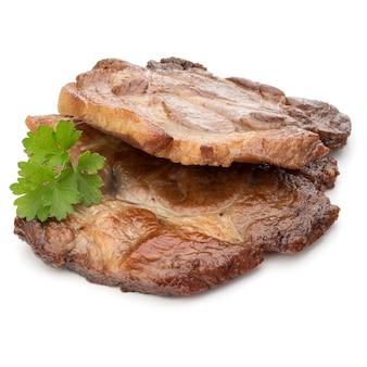 Gekochtes gebratenes schweinefleisch mit petersilienkrautblättern garniert isoliert auf weißem hintergrundausschnitt cut