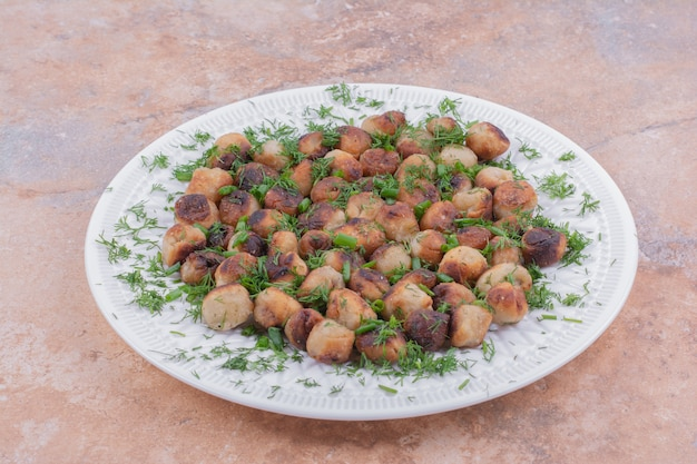 Gekochtes kaukasisches khinkali in weißer schale, serviert mit kräutern und gewürzen.